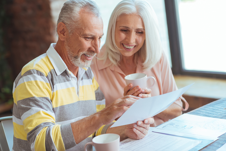 An older couple reviewing a domestic partnership agreement in Phoenix, AZ